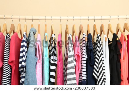 Colorful clothes on hangers in room - stock photo