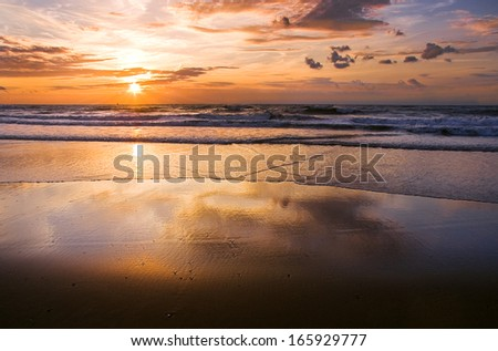 Colorful cloudy sunset at the beach with reflection - horizontal - stock photo