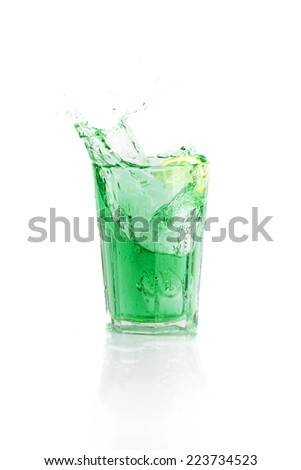 Colorful cocktail the green fairy with splashes. Summer exotic cocktail with ice, lemon and splashes on isolated white background - stock photo