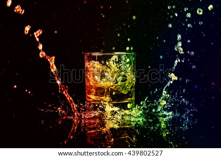 Colorful coctail with ice on darck. Isolated shot of whiskey with splash on black background - stock photo