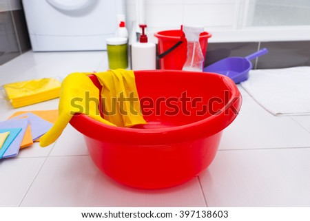Colorful collection of household cleaning products with a red basin, yellow gloves and cloths, assorted containers of chemicals and containers on a clean white tiled floor - stock photo