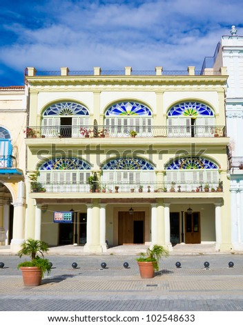 Colorful colonial building in Havana with  distinct traditional architecture elements such as porticoes,balconies and colorful stained glass windows and doors - stock photo