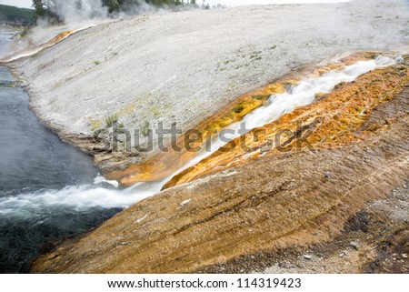 Colorful composition of steaming water falling down a mountain in Yellowstone National Park, Montana, Wyoming, USA - stock photo