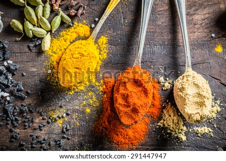 Colorful condiments on old board - stock photo