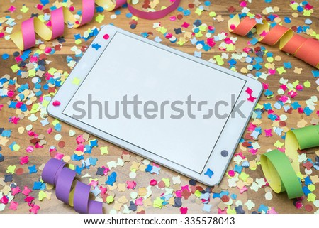 colorful confetti and paper streamers on wooden table with white template on tablet - stock photo