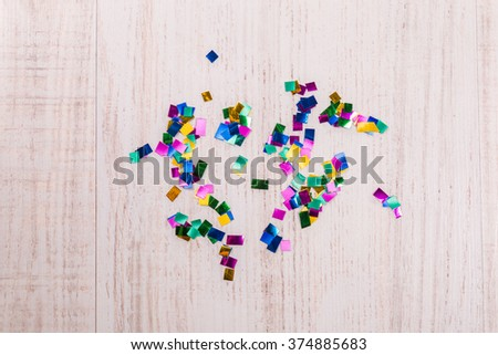 Colorful confetti on wood background - stock photo
