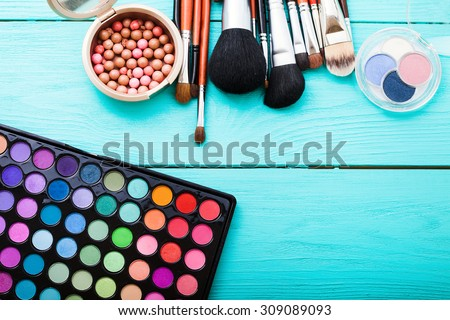 Colorful cosmetics on blue wooden workplace. Top view - stock photo