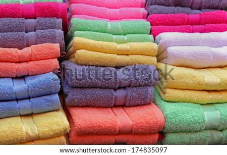 Colorful cotton towels neatly folded on shelf - stock photo