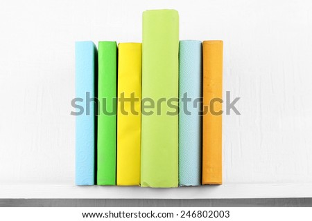 Colorful covered books on bookshelf and white wall background - stock photo