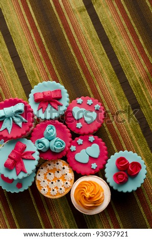 Colorful cup cakes isolated on cotton background - stock photo