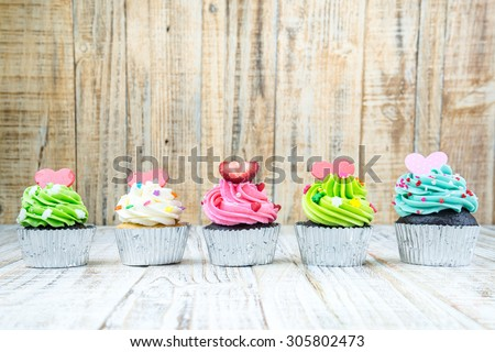 Colorful Cupcake on wood vintage background - stock photo