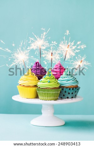 Colorful cupcakes decorated with sparklers - stock photo