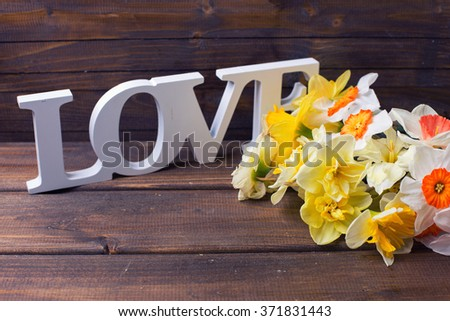 Colorful daffodils  flowers and wooden word love  on brown painted wooden planks. Selective focus. Toned image. - stock photo