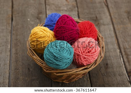 Colorful decorated  in basket easter eggs from wool yarn on wood table. Happy Easter. - stock photo