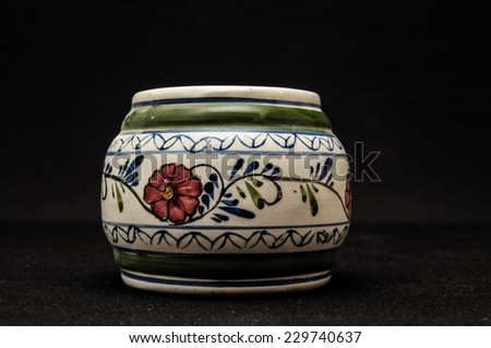Colorful designed clay vase over a Black background - stock photo