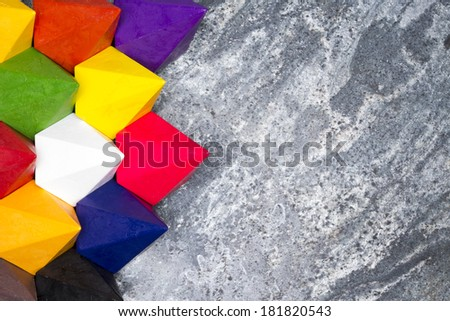 Colorful diamond shaped wax crayons in the colors of the spectrum or rainbow arranged in a tight group as a left hand border on a grey stone background with copy space - stock photo