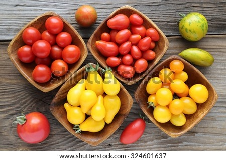 Colorful different kind tomatoes in wooden bowls. - stock photo