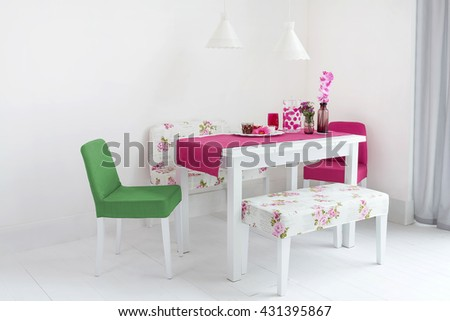 colorful dining table and comfortable chairs in modern home with elegant table setting - stock photo
