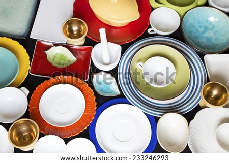 Colorful dishes and utensils on a black background - stock photo