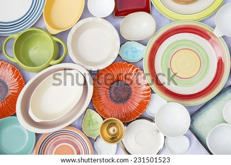 Colorful dishes and utensils on a white cloth - stock photo