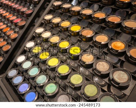 Colorful display of eye makeup in an open shop with eye shadow in all the colors of the spectrum - stock photo