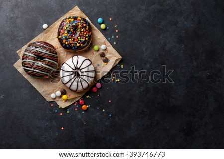 Colorful donuts and candies on stone table. Top view with copy space - stock photo