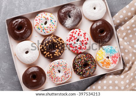 Colorful donuts box on stone table - stock photo
