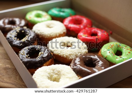 Colorful donuts in box, full box, coconut topping - stock photo