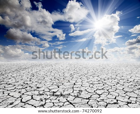 colorful dramatic landscape with cracked soil and blue sky - stock photo