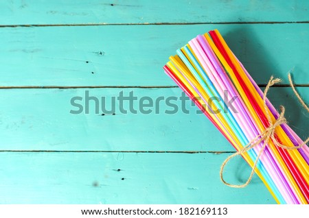 Colorful drinking straws on vibrant table top - stock photo