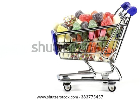 colorful Dutch tum tum candies in shopping cart isolated on white background - stock photo