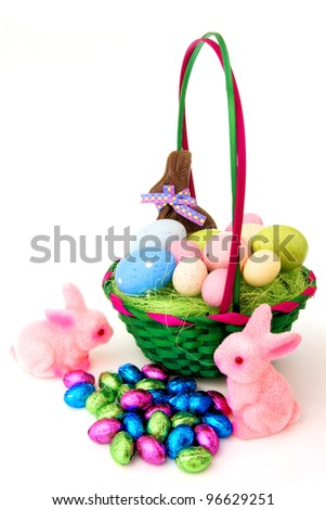 Colorful Easter basket with eggs, candy and bunnies over white - stock photo