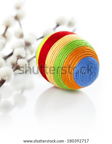 Colorful easter egg covered with woolen yarn. Some catkins in background. - stock photo