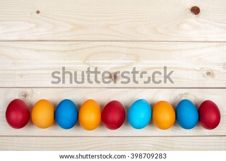 Colorful Easter egg frame on light wooden boards. A row of hand dyed eggs below a copy space - stock photo