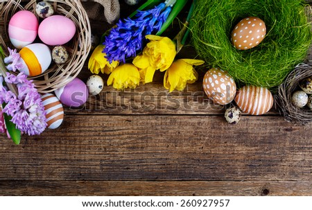 Colorful easter eggs and flowers on wooden background with copyspace - stock photo