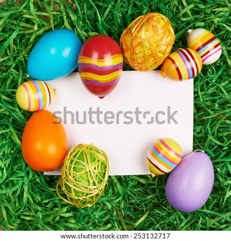 Colorful Easter eggs and green colored ribbons around the white copyspace paper card - stock photo