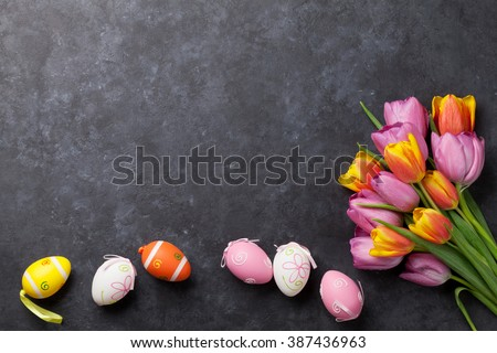 Colorful easter eggs and tulip flowers on stone table. Top view with copy space - stock photo