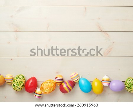 Colorful Easter eggs decoration lying ing line over the wooden surface as a copyspace festive background composition - stock photo