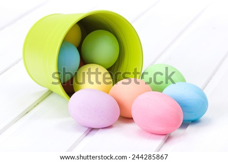 Colorful Easter eggs flowing out from green bucket - stock photo