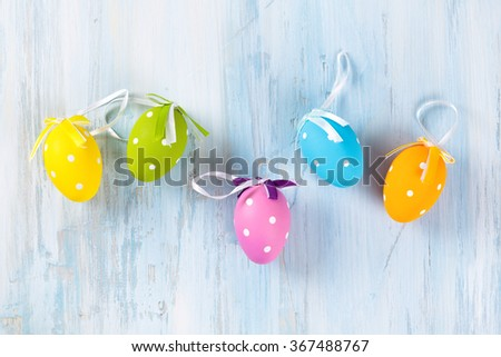 Colorful Easter eggs in a row on wooden background. - stock photo