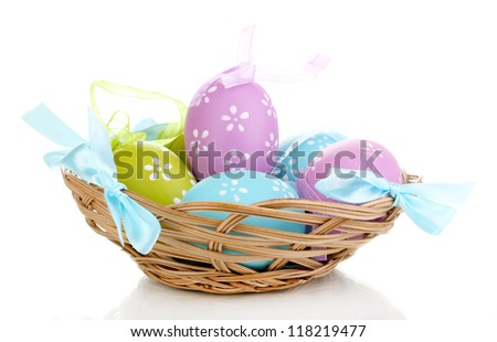 Colorful easter eggs in basket isolated on white - stock photo