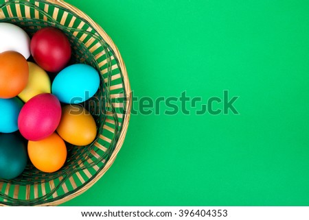 Colorful Easter Eggs in basket on green matte background. Top view - stock photo