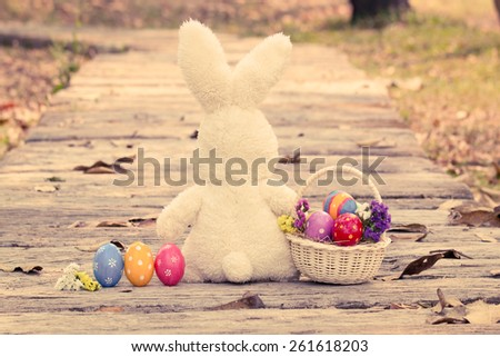 Colorful easter eggs in basket with cute rabbit on wooden pathway in vintage style - stock photo