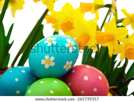 Colorful easter eggs in basket with flowers. Selective focus - stock photo