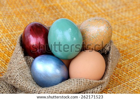 Colorful easter eggs in burlap hessian sacking bag. - stock photo