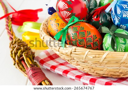 Colorful Easter Eggs in the basket with wicker and bows,  traditional decoration for this spring holiday - stock photo