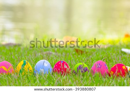 Colorful Easter eggs in the grass on the green water - stock photo