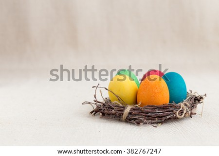 Colorful Easter eggs in the nest on texture background. Soft focus (selective focus)  with copy space for your message,  isolated - stock photo