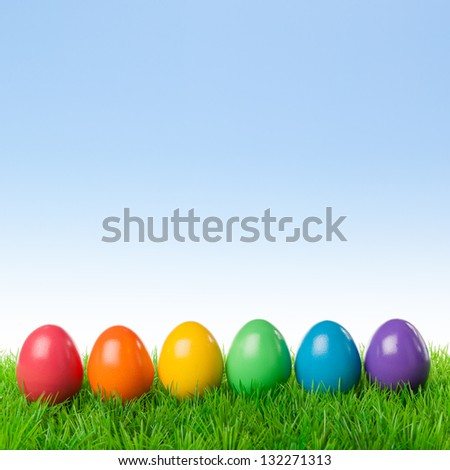 Colorful easter eggs on a fresh meadow, isolated over a bright spring sky. - stock photo