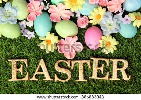Colorful Easter eggs on grass with flowers background - stock photo